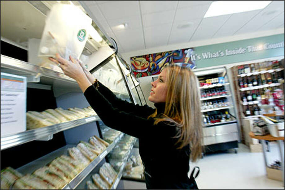 Kara Peters stocks lunches on the shelves at Organic To Go's Issaquah store, 5610 E. Lake Sammamish Parkway S.E. Order at 425-837-9922 or www.organictogo.com. Photo: Phil H. Webber/Seattle Post-Intelligencer