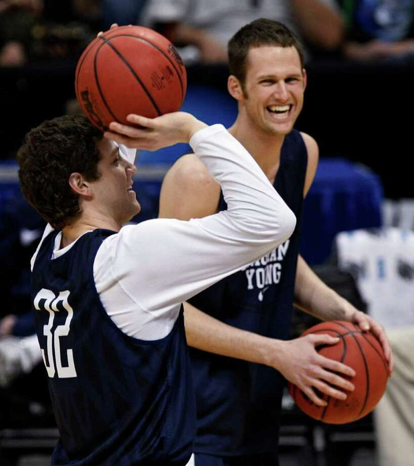 BYU guard Jimmer Fredette, left, and forward Stephen Rogers share a laugh during practice at the Pepsi Center in Denver on Wednesday, March 16, 2011 as they get ready for their NCAA second round tournament basketball game against Wofford on Thursday. (AP Photo/ Ed Andrieski) Photo: Ed Andrieski