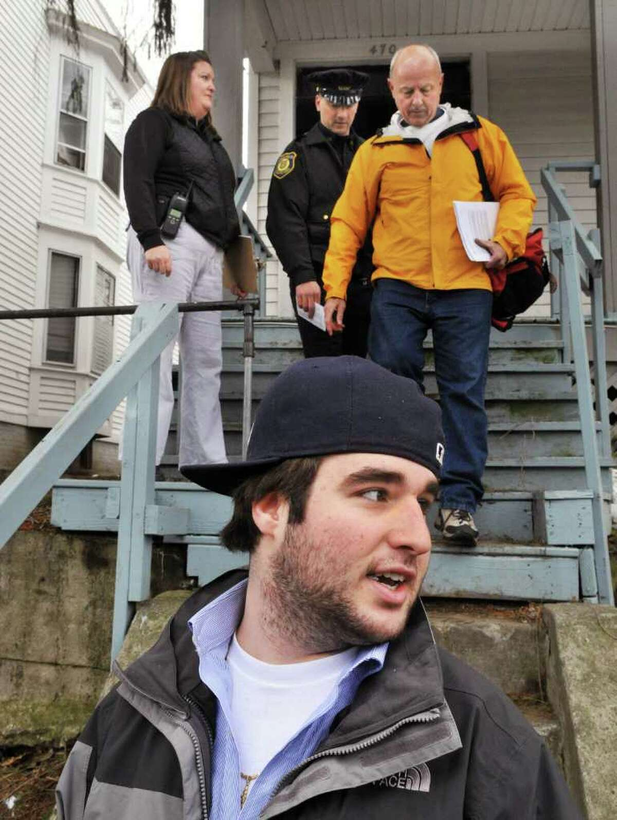 UAlbany student Michael Tropiano, 19, of Albany (in foreground) speaks with reporters as Albany police officers Janet Zalatan, left, and Rich Romand together with UAlbany's director of personal safety and off-campus affairs Thomas Gebhardt (at right) go door to door along Hudson Ave. in Albany Wednesday afternoon March 16, 2011, speaking to students following Saturday morning's melee. (John Carl D'Annibale / Times Union)