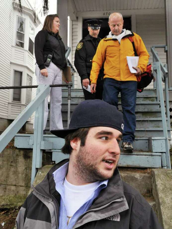 UAlbany student Michael Tropiano, 19, of Albany (in foreground) speaks with reporters as Albany police officers Janet Zalatan, left, and Rich Romand together with UAlbany's director of personal safety and off-campus affairs Thomas Gebhardt (at right) go door to door along Hudson Ave. in Albany Wednesday afternoon March 16, 2011, speaking to students following Saturday morning's melee. (John Carl D'Annibale / Times Union) Photo: John Carl D'Annibale