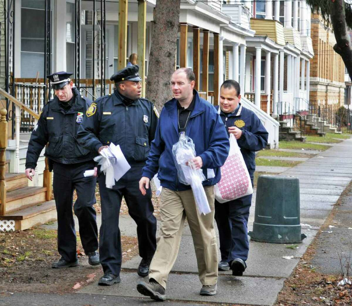Albany police officers, from left, Sgt. Jason Davis, Officer Kelly Kimbrough and Officer Matthew Monesano along with Dave Mankind (at right) from College of St. Rose security go door to door along Hudson Ave. in Albany Wednesday afternoon March 16, 2011, speaking to students following Saturday morning's melee. (John Carl D'Annibale / Times Union)