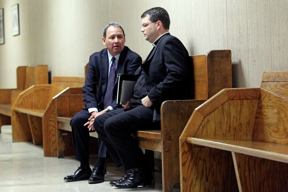 Father Martin Leopold (right) talks with attorney Ron Mendoza before testifying in a nurse's defamation suit against Christus Santa Rosa. Photo: Tom Reel/treel@express-news.net / © 2011 San Antonio Express-News