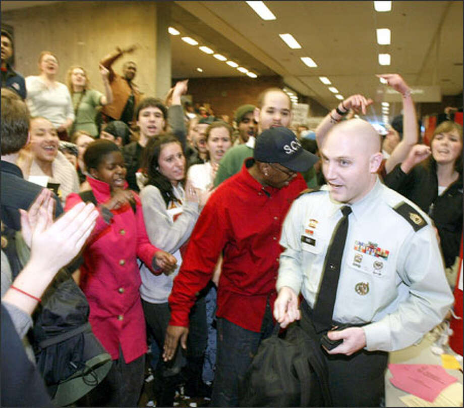 Sgt. 1st Class Jeff Due, right, a U.S. Army recruiter, is surrounded by protesters at Seattle Central Community College on Jan. 20. Photo: / Associated Press / AP