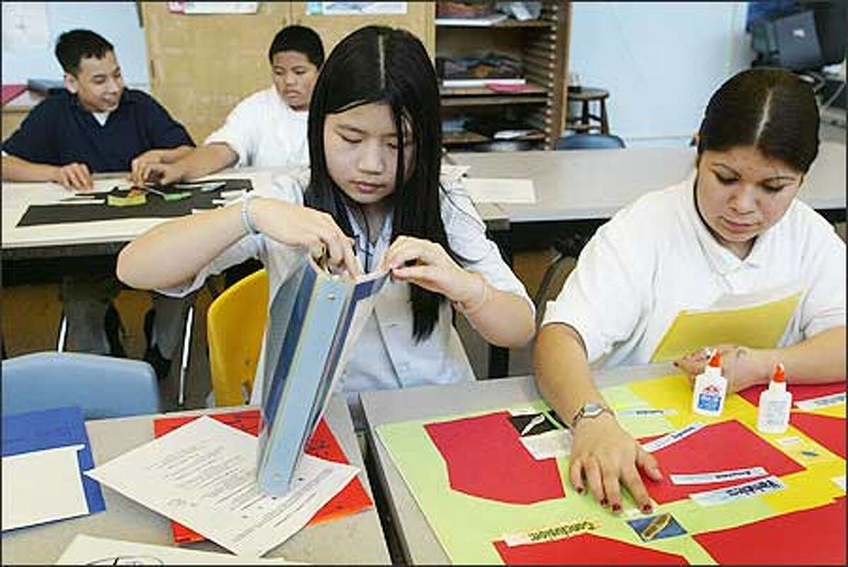 Meany Middle School eighth-graders Ving Hoang, left, and Carolina Fernandez work on a science project recently. The school has only 464 students and hasn't been renovated since it was built in 1955, two factors that make it vulnerable in light of possible closures starting in 2006-07.