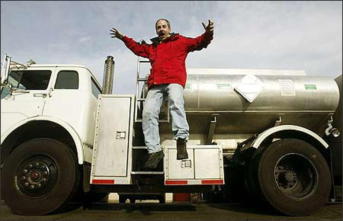 Dan Freeman of Dr. Dan's Alternative Fuel Werks in Ballard jokes around in front of one of his tanker trucks at his business.