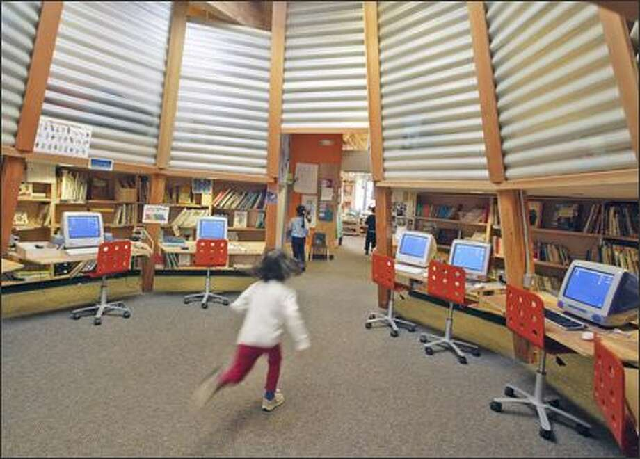 """In a blur, 4-year-old Marika Inouye dashes through the lampshade- shaped computer and library room in the University Child Development School's """"Labyrinth"""" building. Photo: JIM BRYANT/P-I"""
