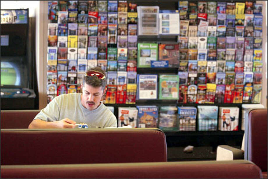 Passenger Michael Anselme eats in front of the brochures on the ferry Wenatchee. Orca Relief Citizens' Alliance brochures can now be in the mix. Photo: Phil H. Webber/Seattle Post-Intelligencer