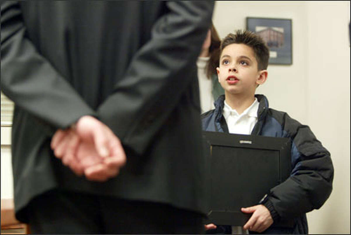 Eight-year-old Perry Ortiz-Williams of Seattle received a plaque from the Plymouth Housing Group for raising $2,000 toward helping the homeless.