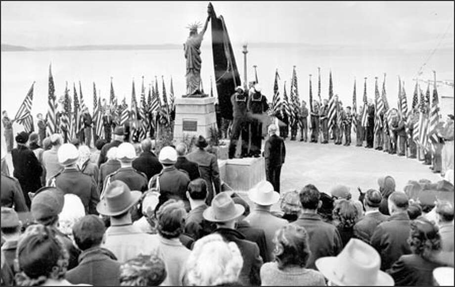 Sea Scouts from the Yankee Clipper lift the canvas from a replica of the Statue of Liberty during dedication ceremonies on Alki Beach Feb. 23, 1952. Photo: / Seattle Post-Intelligencer