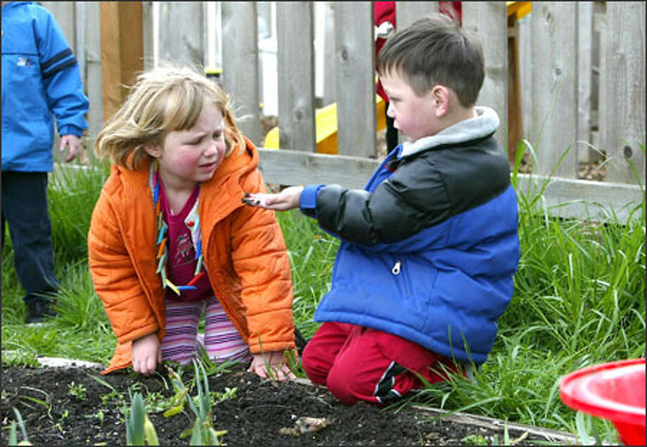Olivia Neumark, left, doesn't appear to share the same fascination with a worm as fellow preschooler Joshua Coulter during a visit to the Hillman City P-patch. Photo: Gilbert W. Arias/Seattle Post-Intelligencer / SEATTLE POST- INTELLIGENCER