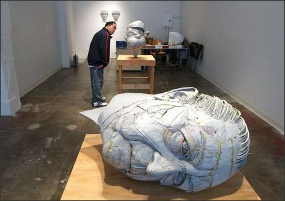 """Andres Ponsoy gets head to head with Scott Fife's """"Popeye"""" in a show at Platform Gallery that closed this week. In the foreground was Fife's """"Mies van der Rohe."""" Photo: GILBERT W. ARIAS/P-I"""
