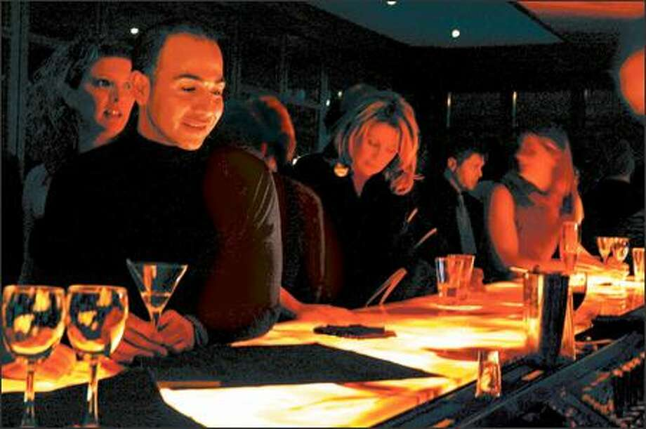 "A young crowd gathers at the underlighted onyx bar at Lift Bar and Grill in Coal Harbor near Stanley Park. The restaurant's menu includes 15 ""whet plates,"" which are larger than typical appetizers. Photo: JANICE MUCALOV"