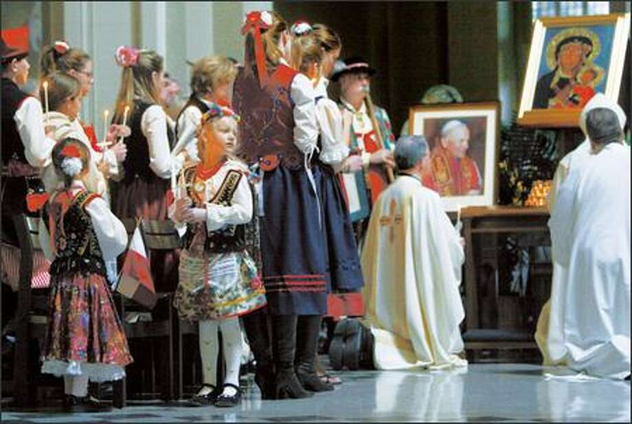 Members of Seattle's Polish Catholic community, including Weronika Wianecka, 5, of Renton, take part in a Mass at St. James Cathedral yesterday to mark the funeral of Pope John Paul II. Archbishop Alexander Brunett presided. Photo: Karen Ducey/Seattle Post-Intelligencer