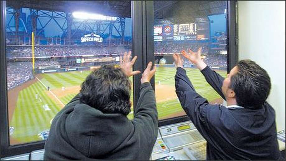 Scoreboard operators Frank Manthou, left, and Mark Johnston reach for a foul ball, which hit the window of their booth and bounced back during a game. Photo: Karen Ducey/Seattle Post-Intelligencer