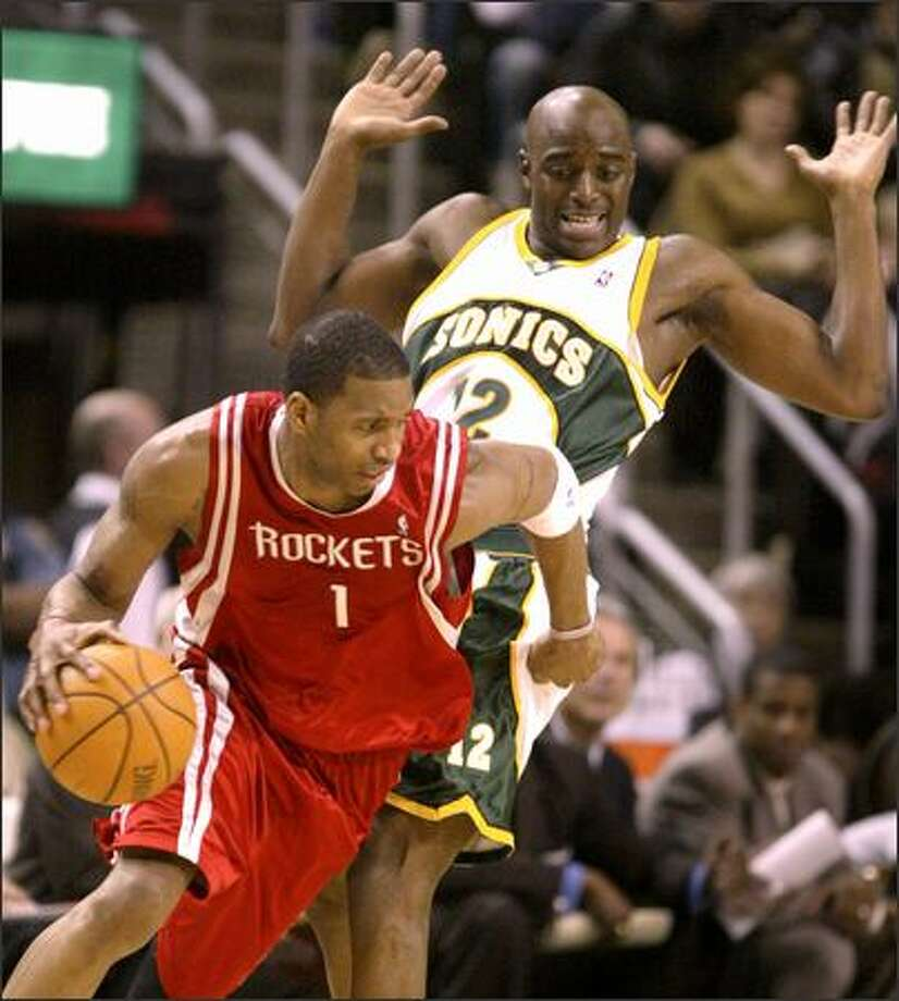 Houston Rockets star Tracy McGrady, who led all scorers with 38 points, drives past Damien Wilkins. Photo: Dan DeLong/Seattle Post-Intelligencer