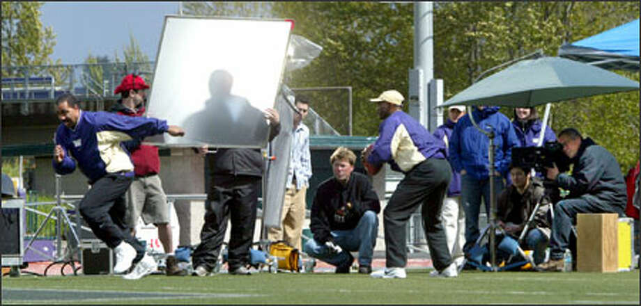 "Washington basketball coach Lorenzo Romar takes off on a pass pattern while new football coach Tyrone Willingham sets up to throw during filming of a ""Return of the Dawgs"" ad campaign promoting ticket sales for the 2005 football season. Photo: Karen Ducey/Seattle Post-Intelligencer"