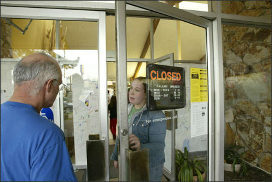 Library assistant Kara Foster tells a reader that he is too late to get into the Ballard Branch Library, which closed so materials can be moved to its new location. Photo: Grant M. Haller/Seattle Post-Intelligencer / Seattle Post-Intelligencer