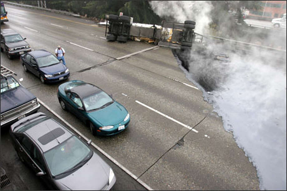 Firefighters stand by as a tow-truck driver inspects hardened roofing tar that spilled onto northbound Interstate 5 in Seattle after a tanker lost its trailer.  The freeway was closed to traffic for about four hours. Photo: Grant M. Haller/Seattle Post-Intelligencer / AARON HUEY