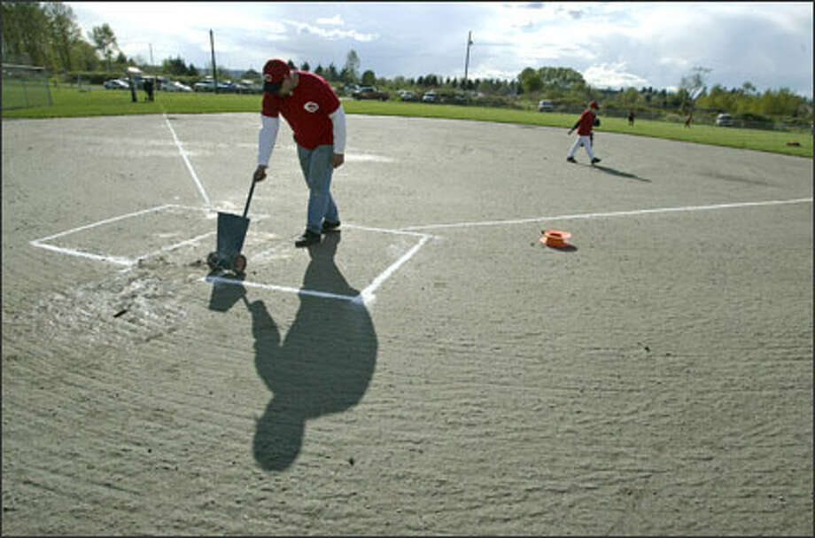 Kurt Lanter, a manager in the North Snohomish Little League, lays down the lines for the batting box before a game yesterday at a field built illegally on farmland near Snohomish. Photo: Grant M. Haller/Seattle Post-Intelligencer