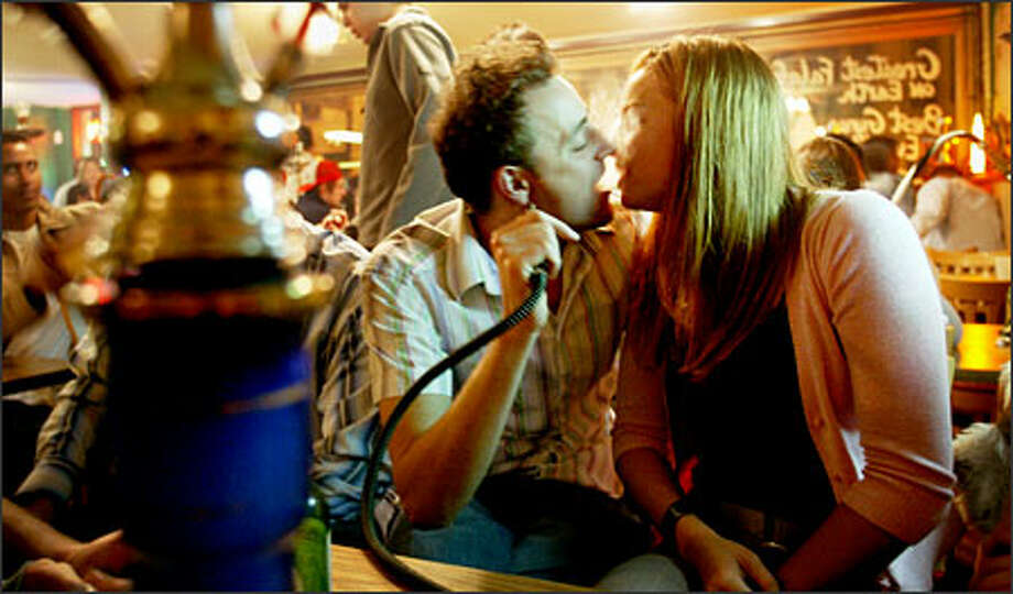 Catalin Lazar of Kirkland and Mary David of Mercer Island exchange smoke while enjoying a hookah at Zaina Food, Drink & Friends in Pioneer Square. Photo: Dan DeLong/Seattle Post-Intelligencer