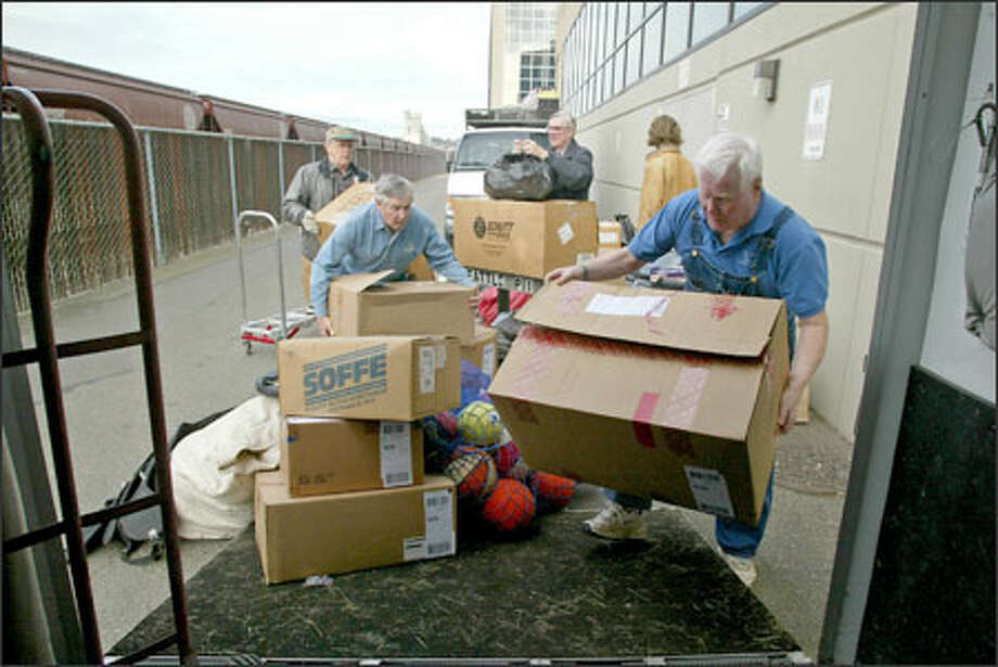 Johnny O'Brien (left rear), Edward O'Brien (left center), Thomas Cunningham (center rear) and Buzz Larson (right front) load donated athletic gear into a trailer last month. Photo: Gilbert W. Arias/Seattle Post-Intelligencer / SEATTLE POST- INTELLIGENCER