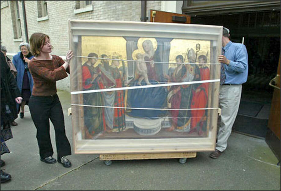 A Renaissance painting is brought into St. James Cathedral after a parade yesterday celebrating the 15th-century artwork's restoration and return. Photo: Gilbert W. Arias/Seattle Post-Intelligencer / SEATTLE POST- INTELLIGENCER