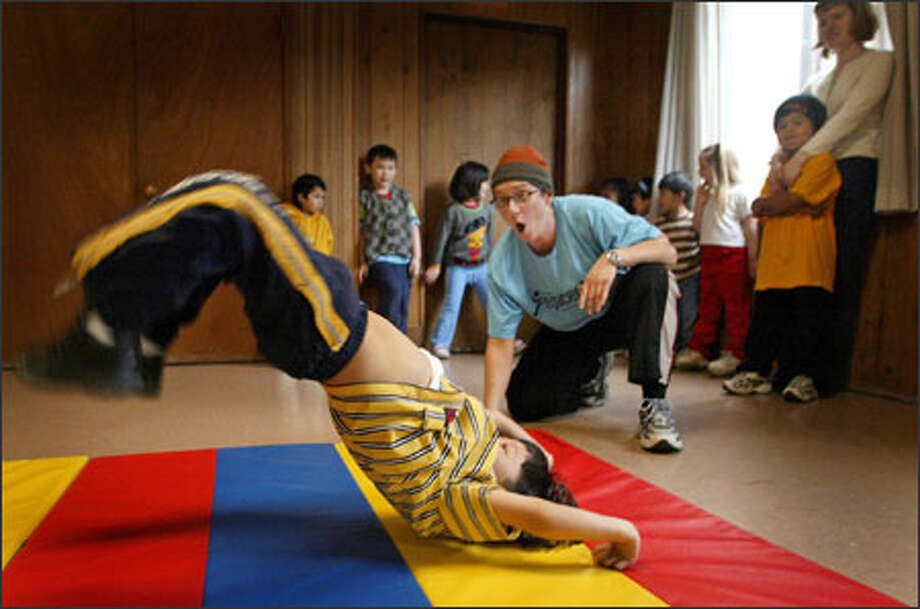 Arts instructor Sonya Boothroyd watches as Alexis Orozco, 4, performs a flip and dance move during Urban Dance yesterday at the Refugee and Immigrant Center in Seattle. The state-funded center provides a free day care program for children in poor families. Photo: Joshua Trujillo/Seattle Post-Intelligencer / Seattle Post-Intelligencer