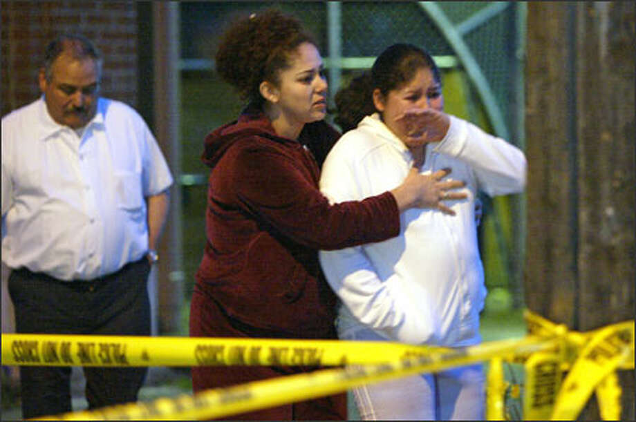 An unidentified woman tries to comfort the sister of a shooting victim in South Park last night. Police say two teenagers were stopped at a red light when their car was fired upon. Photo: Mike Urban/Seattle Post-Intelligencer / Seattle Post-Intelligencer