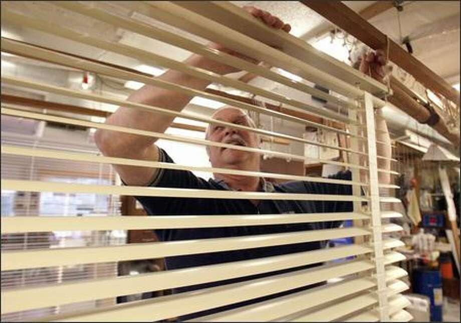 Sam Abbott, owner of Airlight Venetian Blind Co. in North Ballard, works on some 1920 Venetian blinds that he is repairing for a customer from Oregon. Photo: PHIL H. WEBBER/P-I
