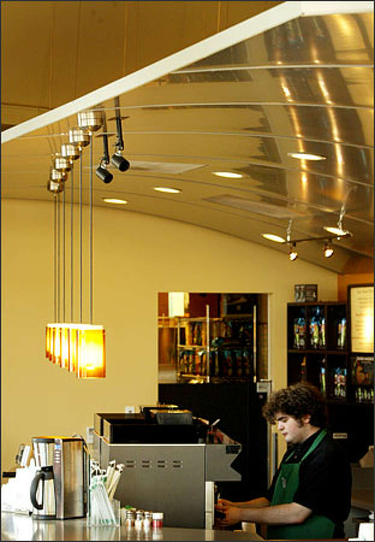 Alec Whitney prepares a drink at Starbucks on 2344 Eastlake Ave., where an elegantly curved aluminum wing over the bar functions both as a dropped ceiling and sculptural intrusion.