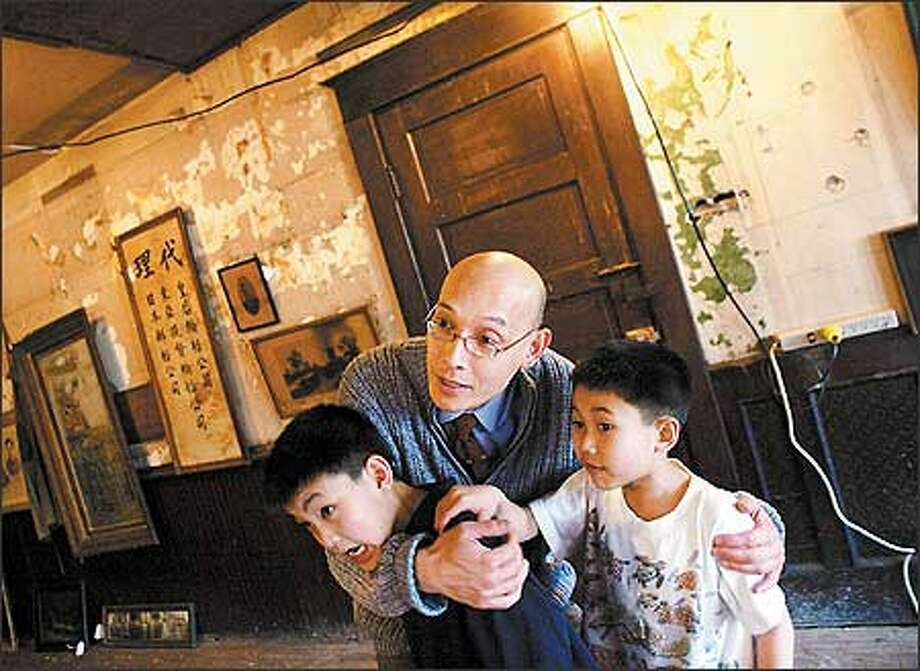 Ron Chew and his sons, Cian, 9, left, and Kino, 7, huddle as they hear noises from an old window shutter blowing outside one of the Kong Yick buildings yesterday. The building, constructed in 1910, was once a hotel for single men. The Wing Luke Asian Museum, where Chew works, plans to renovate it and turn it into a community showcase. Photo: Karen Ducey/Seattle Post-Intelligencer