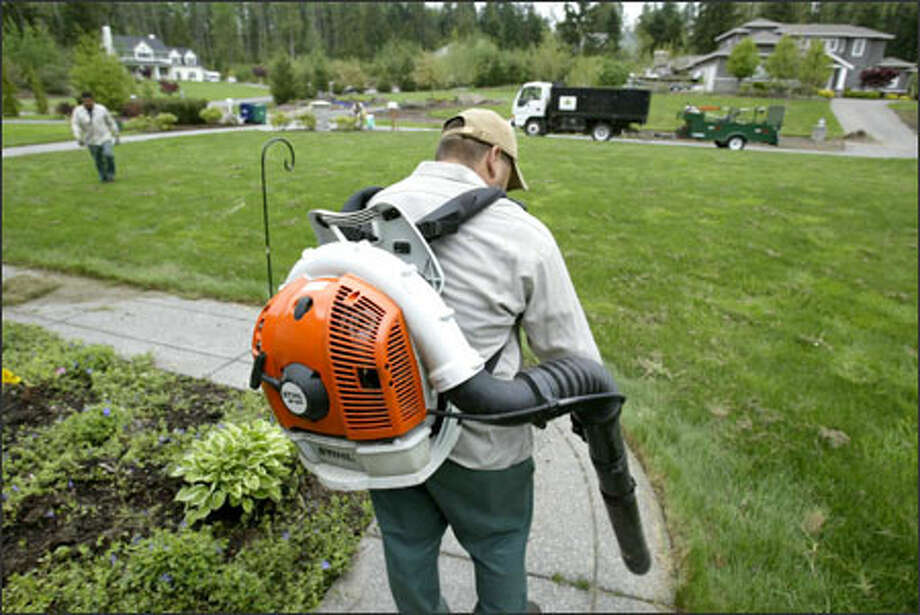 Edwardo Birgen, working at a home near Lake Joy in Carnation, is among the employees at Jebco Horticultural Services, a company facing a crisis over the cost of gasoline. Photo: Mike Urban/Seattle Post-Intelligencer / Seattle Post-Intelligencer