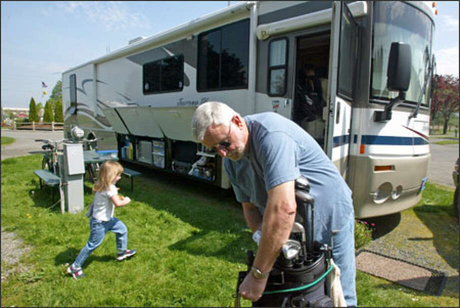 Chuck Butler arranges his golf clubs outside his motor home at the KOA campground in Kent while his granddaughter Amanda Johnson, 3, runs around. Butler and his wife sold their house in Federal Way after they retired. They now live in the motor home. Photo: Karen Ducey/Seattle Post-Intelligencer