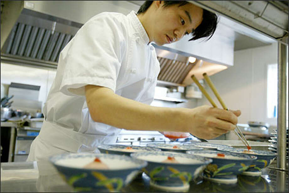 Taro Iesaka, chef for the consul general of Japan, planned an elaborate menu for the traditional kaiseki ryori feast. Some ingredients came from Japan, including cherry blosssoms, rice vinegar and fish, which was flown in from Tokyo's famous Tsukiji fish market. Photo: Paul Joseph Brown/Seattle Post-Intelligencer