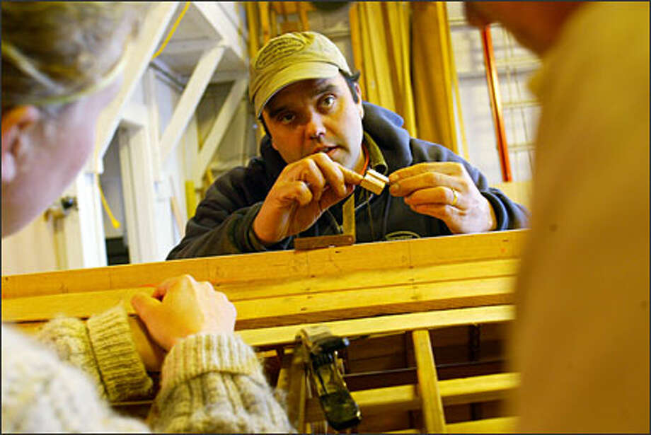 Tim Lee shows students how to measure plank-edge bevels on a 1917 skiff. Photo: Grant M. Haller/Seattle Post-Intelligencer