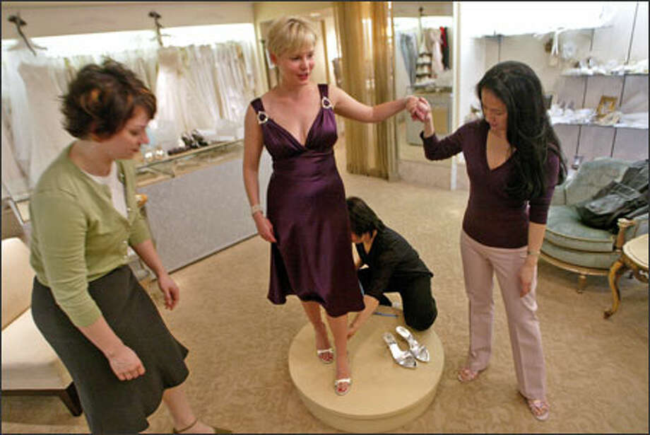 Designer and shop owner Luly Yang, far right, helps a customer with a fitting. Yang last fall moved her store to a larger spot at Fourth and University. Photo: Karen Ducey/Seattle Post-Intelligencer