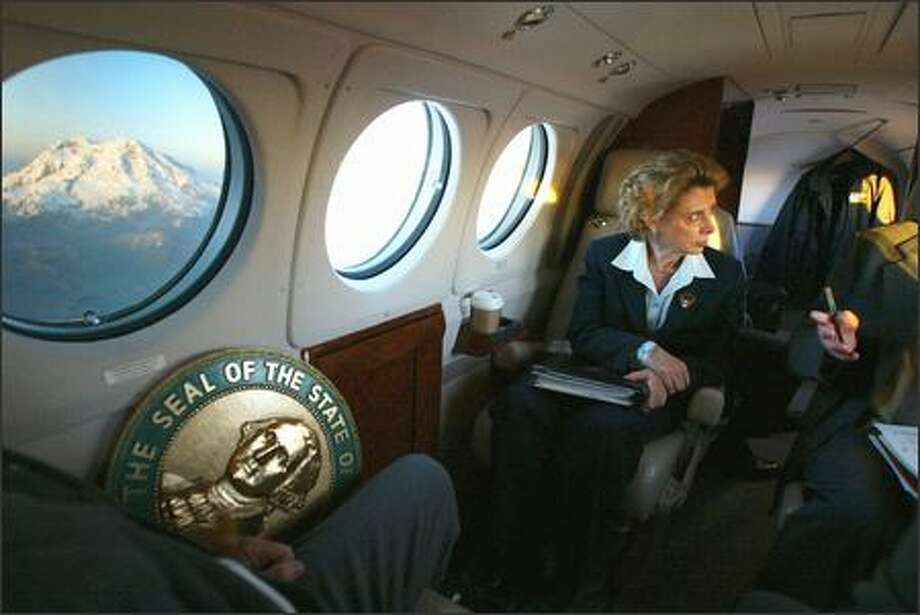 With Mount Rainier aglow in sunlight, Gov. Christine Gregoire focuses on a policy discussion during a return flight from Yakima to Olympia in March. She took a few brief moments to enjoy the view of the mountain, but soon after went back to work with Keith Phillips, her environmental policy adviser. View a gallery of 21 photos of the governor behind the scenes. Photo: Meryl Schenker/Seattle Post-Intelligencer