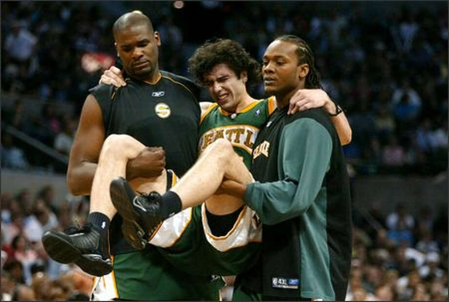 Vladimir Radmanovic is carried off the court by Jerome James, left, and Danny Fortson after rolling his ankle during the second quarter. He could be sidelined for the rest of the series. Photo: Joshua Trujillo/Seattle Post-Intelligencer