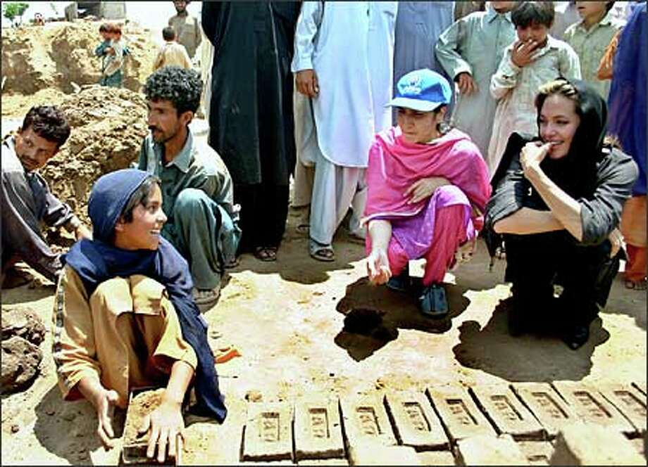 Other stars frolic on beaches or get pampered at spas. But UN goodwill ambassador Angelina Jolie, at right, instead spends time with an Afghan girl at a brick kiln near a refugee camp outside Islamabad, Pakistan. (UNITED NATIONS HIGH COMMISSIONER FOR REFUGEES VIA AP) Photo: / Associated Press