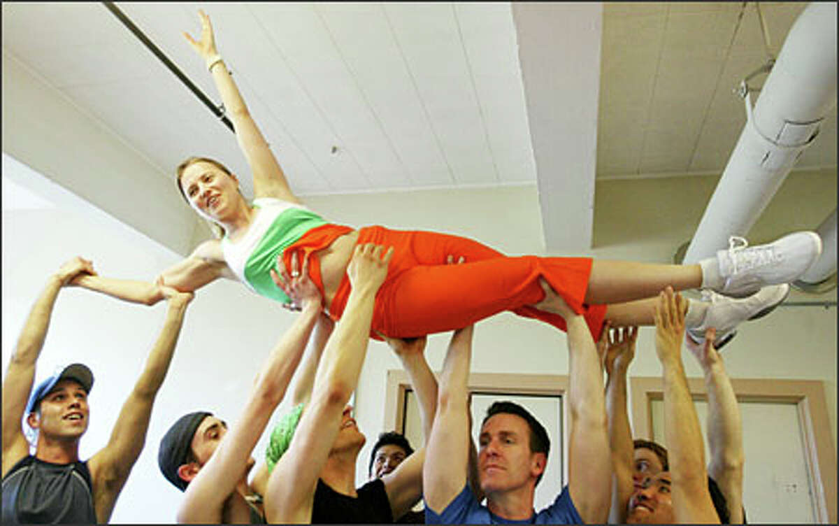 """Lucy Lawless is lifted into the air as she rehearses a chorus dance number for """"Gentlemen Prefer Blondes"""" at the 5th Avenue Theatre."""