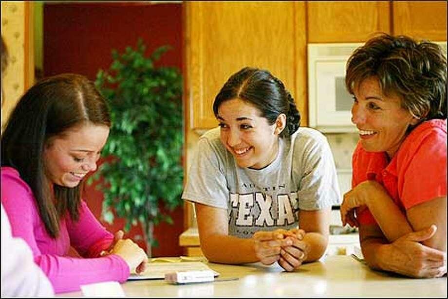 Natasha Slesk, 16, center, shares a light-hearted moment with her friend, Kelsey Leenders, 18, left, and her mother, Jamie Slesk, at their Ferndale home. Photo: Karen Ducey/Seattle Post-Intelligencer