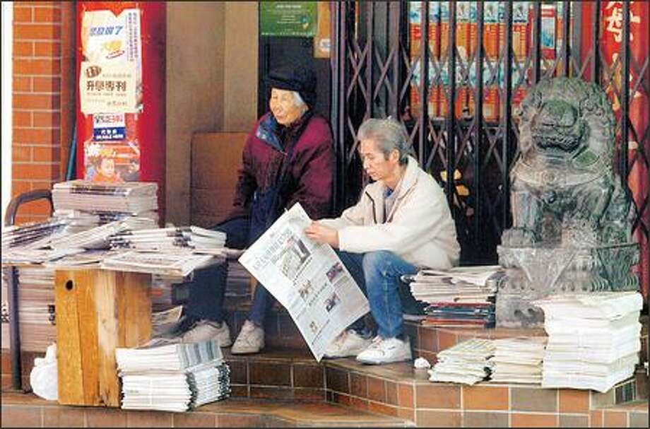 With stacks of Chinese language newspapers close to the sidewalk and passers-by, a vendor reads a paper before they're all sold out. Photo: Jeff Larsen/Seattle Post-Intelligencer