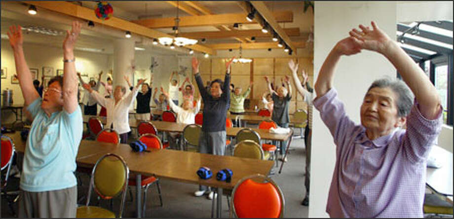 Seniors work out during the Lifetime Fitness Program at Kawabe Memorial House in Seattle. The class is designed to maintain strength and flexibility. Photo: Karen Ducey/Seattle Post-Intelligencer