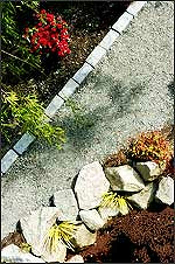 Salt-and-pepper granite bricks along a footpath keep base rock from creeping into a flower bed. Opposite the bricks are granite stones bordering a pond. Photo: Steve Shelton