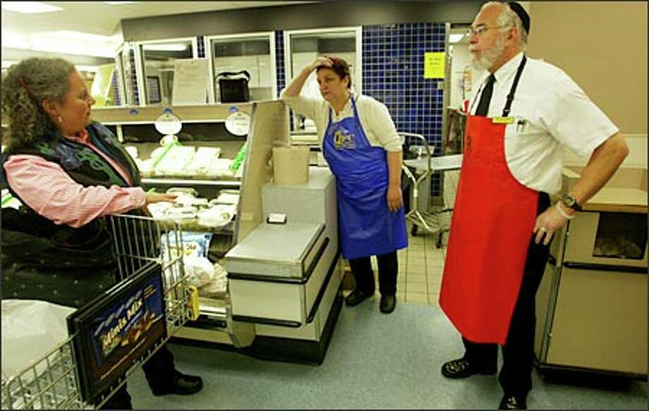 From left, Lynn Gottlieb of Seattle talks with deli worker Davydova Shifro and Ken Kolman, manager of the kosher department, at QFC in Rainier Beach yesterday. Photo: Karen Ducey/Seattle Post-Intelligencer