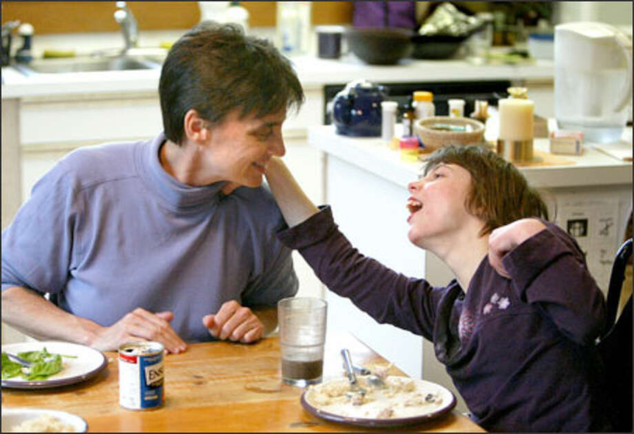 Wendy Harris helps her foster daughter Melissa with dinner, which includes a can of Ensure. The 15-year-old, who has cerebral palsy, gets the nutrition supplement to help her keep her weight up. The supplement is paid for in a Medicaid program the state is considering scaling back. Photo: Scott Eklund/Seattle Post-Intelligencer / Seattle Post-Intelligencer