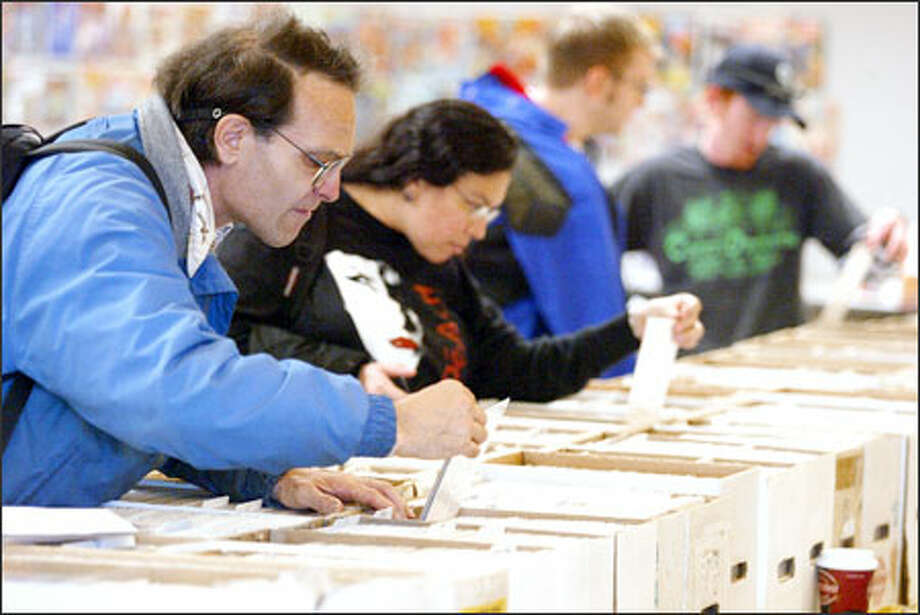 Mark Whitaker looks for vintage Superman, Superboy or Tarzan comic books at the ComiCard Convention yesterday. Estelle McDermott wanted X-Men or Wolverine titles. Photo: Paul Joseph Brown/Seattle Post-Intelligencer