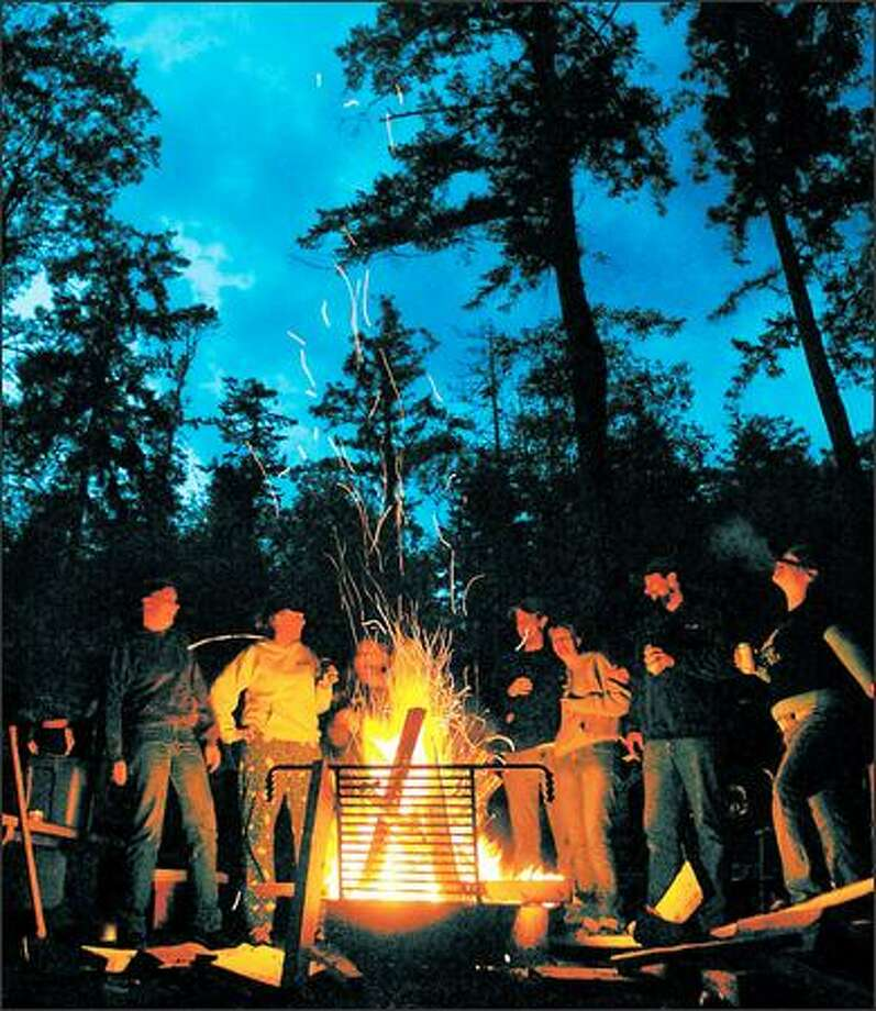 Friends gather round the campfire for drinks and stories at Deception Pass State Park on Whidbey Island. Photo: JOSHUA TRUJILLO/P-I
