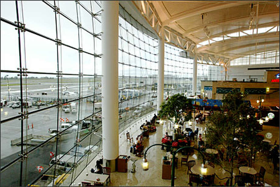 The Central Terminal's 60-by-350-foot glass wall offers a spectacular view of the activity on Sea-Tac Airport runways. The panes compose a compound curve, convex in the vertical plane and concave in the horizontal. Photo: Gilbert W. Arias/Seattle Post-Intelligencer