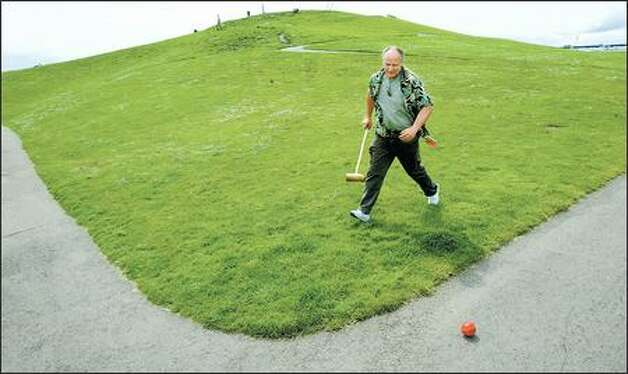 "Dan Whited chases down his runaway ball during an extreme croquet match at Gas Works Park between six doubles teams of the Lakewood Croquet Club. Though a rookie, Whited quickly adapts to the club's rule to ""always cheat."" Photo: PAUL JOSEPH BROWN/P-I"